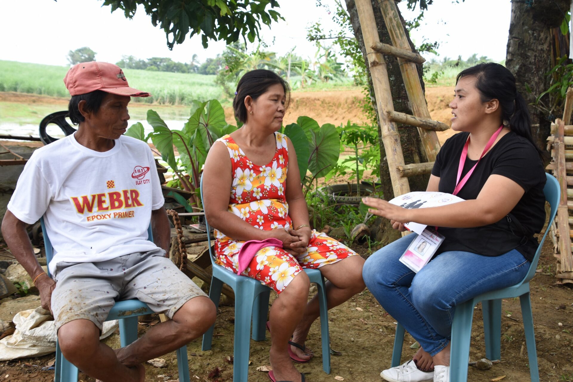 A Graduation Community Facilitator (GCF) in Negros Occidental province, Philippines works with a program participant and her husband on life-skills and business training.
