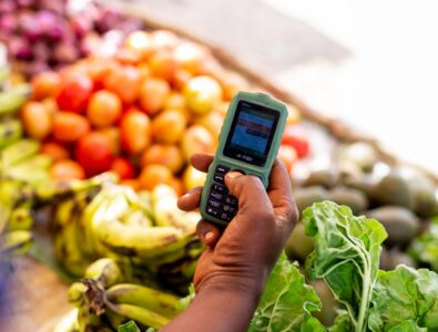 Person holding phone over a stand of fruit and vegetables