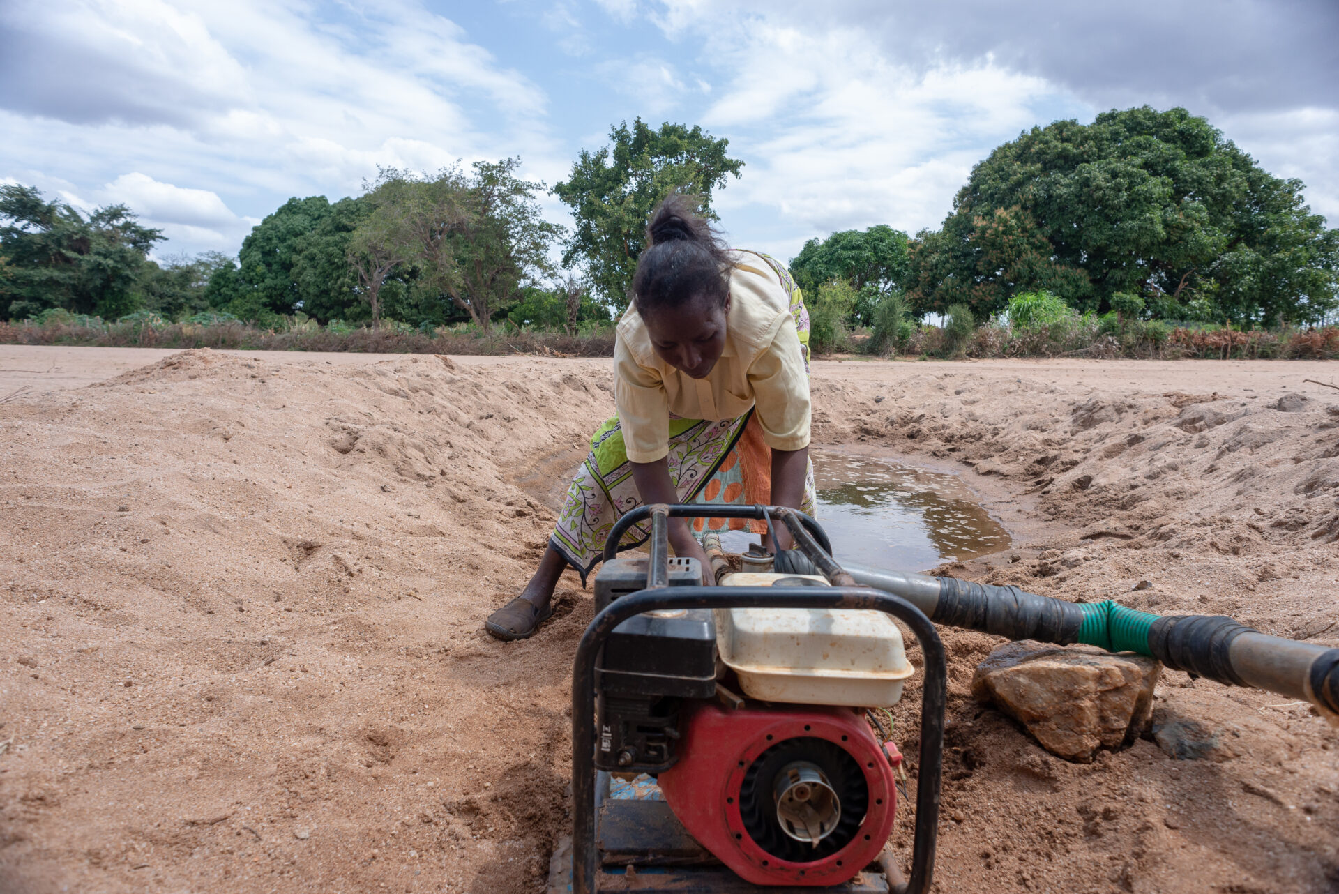 A women works in a dry riverbed to start up her water pump to irrigate crops